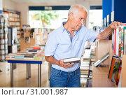 Купить «Portrait of intelligent older man choosing necessary books on shelves in library», фото № 31001987, снято 11 июня 2018 г. (c) Яков Филимонов / Фотобанк Лори