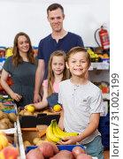 Купить «Smiling preteen boy showing fresh delicious bananas», фото № 31002199, снято 23 июня 2018 г. (c) Яков Филимонов / Фотобанк Лори