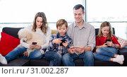 Family members spending time playing with smartphones. Стоковое фото, фотограф Яков Филимонов / Фотобанк Лори