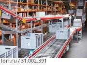 Купить «Automated warehouse. Boxes with spare parts moving on conveyer», фото № 31002391, снято 3 февраля 2017 г. (c) Дмитрий Калиновский / Фотобанк Лори