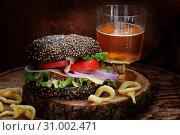 Черный бургер с пивом и луковым кольцами. Стоковое фото, фотограф Марина Володько / Фотобанк Лори