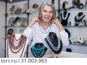 Купить «Woman trying on a aventurine necklace and earrings at a jewelry store», фото № 31003983, снято 2 мая 2019 г. (c) Яков Филимонов / Фотобанк Лори