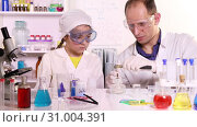 Купить «A young teacher conducts a chemistry lesson in primary school», видеоролик № 31004391, снято 25 июня 2019 г. (c) Алексей Кузнецов / Фотобанк Лори