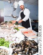 Купить «Standing positive man shows the fish counter», фото № 31005835, снято 27 октября 2016 г. (c) Яков Филимонов / Фотобанк Лори