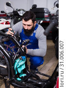 Купить «Worker repairing motorbike», фото № 31006007, снято 19 августа 2019 г. (c) Яков Филимонов / Фотобанк Лори