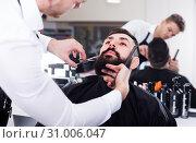 Купить «Happy stylist creating shape for beard of client», фото № 31006047, снято 27 января 2017 г. (c) Яков Филимонов / Фотобанк Лори