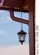 Купить «Металлический фонарь, свисающий на цепи с крыши деревенского дома, на фоне голубого неба», фото № 31006399, снято 23 июня 2019 г. (c) Наталья Николаева / Фотобанк Лори