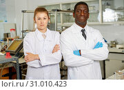 Купить «Experienced male and female scientists standing in laboratory», фото № 31010423, снято 21 марта 2019 г. (c) Яков Филимонов / Фотобанк Лори