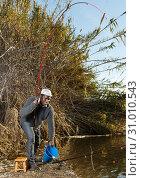 Afro fisherman pulling fish. Стоковое фото, фотограф Яков Филимонов / Фотобанк Лори