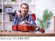 Купить «Young handsome repairman repairing cello», фото № 31044431, снято 4 апреля 2019 г. (c) Elnur / Фотобанк Лори