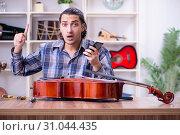 Купить «Young handsome repairman repairing cello», фото № 31044435, снято 4 апреля 2019 г. (c) Elnur / Фотобанк Лори