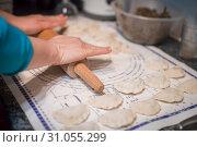 Купить «Close up of woman hands holding rolling pin and preparing traditional polish christmas dish called pierogi, dumplings filled with mushroom and onion filling», фото № 31055299, снято 23 декабря 2017 г. (c) easy Fotostock / Фотобанк Лори