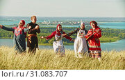 Купить «Young ensemble in traditional russian clothes dancing on the field by the music», видеоролик № 31083707, снято 20 июля 2019 г. (c) Константин Шишкин / Фотобанк Лори