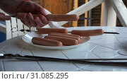 Купить «Cook stringing sausages on a skewer for barbecue. Quick shot», видеоролик № 31085295, снято 19 ноября 2018 г. (c) Aleksandr Sulimov / Фотобанк Лори