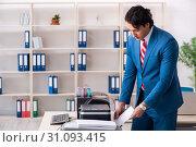Купить «Young employee making copies at copying machine», фото № 31093415, снято 14 декабря 2018 г. (c) Elnur / Фотобанк Лори