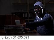 Купить «Male thief in balaclava in the office night time», фото № 31095091, снято 22 апреля 2019 г. (c) Elnur / Фотобанк Лори