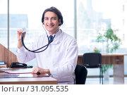 Купить «Young handsome doctor working in the clinic», фото № 31095535, снято 29 апреля 2019 г. (c) Elnur / Фотобанк Лори