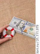 Купить «Life preserver in hand over the banknote bundle of US dollar», фото № 31111979, снято 18 февраля 2017 г. (c) easy Fotostock / Фотобанк Лори