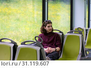 Купить «A handsome guy rides a suburban train, sits and looks out the window, outside the window is a blooming spring meadow.», фото № 31119607, снято 11 июня 2016 г. (c) easy Fotostock / Фотобанк Лори