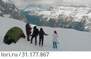 Купить «Young friends set a tent on a mountain - standing outside and having fun - a man playing guitar - Dolomites, Italy», видеоролик № 31177867, снято 22 июля 2019 г. (c) Константин Шишкин / Фотобанк Лори