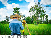 Купить «Asian smart engineer or surveyor in black jeans and long sleeve shirt and woven bamboo hat. He is working on controller screen for surveying land in rice field, Thailand. GPS surveying instrument.», фото № 31179955, снято 26 сентября 2017 г. (c) easy Fotostock / Фотобанк Лори