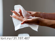 Young woman cleaning hands with wet wipes. Стоковое фото, фотограф YAY Micro / easy Fotostock / Фотобанк Лори