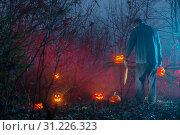 Купить «scary man in night forest is cutting Halloween pumpkins», фото № 31226323, снято 10 ноября 2018 г. (c) Майя Крученкова / Фотобанк Лори