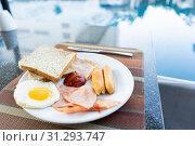 Купить «Delicious Breakfast set by the swimming pool at Pattaya, Thailand», фото № 31293747, снято 28 сентября 2018 г. (c) easy Fotostock / Фотобанк Лори