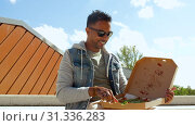 Купить «indian man eating pizza and drinking beer outdoors», видеоролик № 31336283, снято 30 июня 2019 г. (c) Syda Productions / Фотобанк Лори
