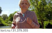 Купить «senior woman with earphones running in summer park», видеоролик № 31379355, снято 1 июля 2019 г. (c) Syda Productions / Фотобанк Лори