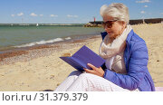 Купить «happy senior woman reading book on summer beach», видеоролик № 31379379, снято 1 июля 2019 г. (c) Syda Productions / Фотобанк Лори