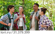 Купить «friends with backpacks on hike talking in forest», видеоролик № 31379399, снято 29 июня 2019 г. (c) Syda Productions / Фотобанк Лори
