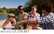 Купить «friends with drinks on wooden pier at lake», видеоролик № 31379451, снято 29 июня 2019 г. (c) Syda Productions / Фотобанк Лори