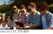 Купить «friends with tablet pc on wooden terrace in summer», видеоролик № 31379459, снято 29 июня 2019 г. (c) Syda Productions / Фотобанк Лори