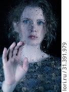 Купить «Sad young woman behind the window glass with raindrops», фото № 31391979, снято 9 июня 2019 г. (c) Serg Zastavkin / Фотобанк Лори