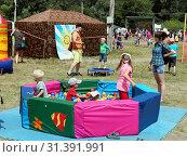 Купить «На детской площадке Грушинского фестиваля дети играют в сухом бассейне, наполненном разноцветными шариками», фото № 31391991, снято 6 июля 2019 г. (c) Светлана Кириллова / Фотобанк Лори