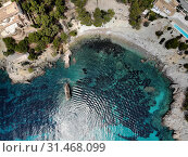 Купить «Cala en Cranc rocky seaside in the Palma de Mallorca directly from above drone point of view photo, picturesque nature stony beach turquoise Mediterranean waters from top image, Balearic Islands Spain», фото № 31468099, снято 28 мая 2019 г. (c) Alexander Tihonovs / Фотобанк Лори