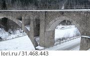 Купить «Старинный каменный арочный железнодорожный мост и автомобильная дорога под ним», видеоролик № 31468443, снято 10 июля 2019 г. (c) Mikhail Erguine / Фотобанк Лори