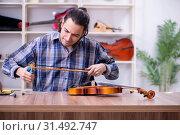 Купить «Young handsome repairman repairing violin», фото № 31492747, снято 4 апреля 2019 г. (c) Elnur / Фотобанк Лори