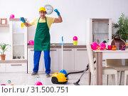 Купить «Young male contractor doing housework after party», фото № 31500751, снято 14 марта 2019 г. (c) Elnur / Фотобанк Лори