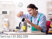 Купить «Young man repairing kettle in service centre», фото № 31502339, снято 27 февраля 2019 г. (c) Elnur / Фотобанк Лори