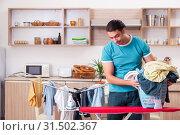 Купить «Young man husband doing clothing ironing at home», фото № 31502367, снято 25 февраля 2019 г. (c) Elnur / Фотобанк Лори