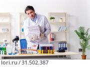 Купить «Young male chemist working in the lab», фото № 31502387, снято 20 февраля 2019 г. (c) Elnur / Фотобанк Лори
