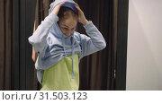 Купить «Pretty young beautiful woman trying on blue sweatshirt, shopping, casual clothes», видеоролик № 31503123, снято 2 июля 2019 г. (c) Ирина Мойсеева / Фотобанк Лори