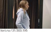 Купить «Pretty woman tries on a blue sweatshirt spinning in front of a mirror, shopping», видеоролик № 31503195, снято 2 июля 2019 г. (c) Ирина Мойсеева / Фотобанк Лори