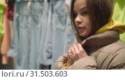 Купить «Pretty young beautiful woman trying on short spring brown down jacket, shopping», видеоролик № 31503603, снято 2 июля 2019 г. (c) Ирина Мойсеева / Фотобанк Лори