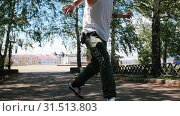 Купить «Young attractive man with tattoos freestyle dancing in the park and walking forward - buildings on the background», видеоролик № 31513803, снято 18 июля 2019 г. (c) Константин Шишкин / Фотобанк Лори