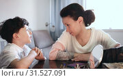Купить «Cheerful woman telling funny story to her teenage son at home table», видеоролик № 31527091, снято 26 апреля 2019 г. (c) Яков Филимонов / Фотобанк Лори