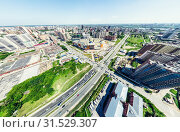Купить «Aerial city view with crossroads and roads, houses, buildings, parks and parking lots. Sunny summer panoramic image», фото № 31529307, снято 22 июля 2019 г. (c) Александр Маркин / Фотобанк Лори
