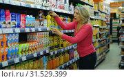 Купить «Casual mature woman shopping for sweet drinks at supermarket food department», видеоролик № 31529399, снято 7 февраля 2019 г. (c) Яков Филимонов / Фотобанк Лори
